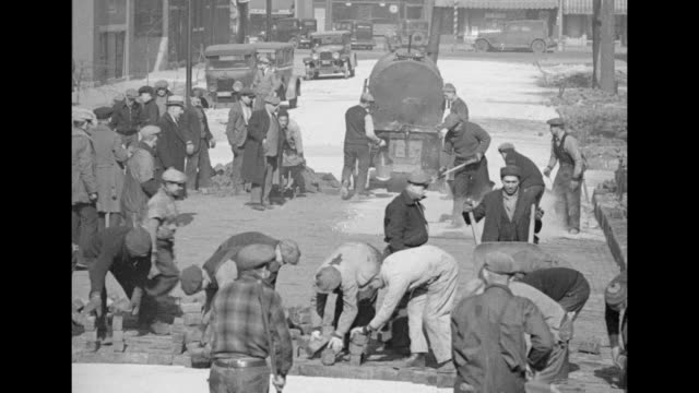 two shots of workers tearing up old pavement in street / workers lining up outside church / workers walking down street towards church / workers in... - pavement点の映像素材/bロール