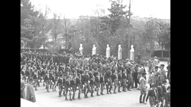vídeos de stock, filmes e b-roll de two shots of young blackshirt boys marching in formation down street past adult blackshirts and officers with benito mussolini among officers / note... - benito mussolini