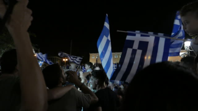 vidéos et rushes de two shots sequence showing crowds of supporters of 'oxi' celebrating in central athens. wide shot showing people waving greek flags and celebrating... - athens greece