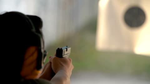 slo mo - two shots shooting handgun pistol at target range - handgun stock videos & royalty-free footage