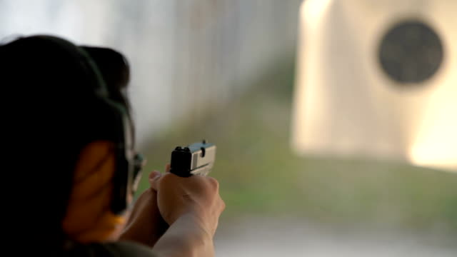 slo mo - two shots shooting handgun pistol at target range - sparare video stock e b–roll