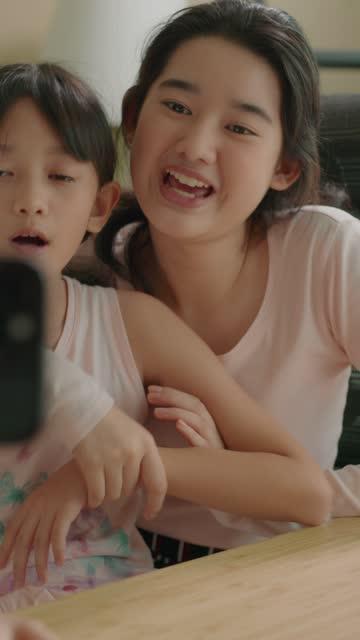 zwei geschwister influencer vlogging, die social-media-inhalte auf dem handy aufnehmen - content stock-videos und b-roll-filmmaterial