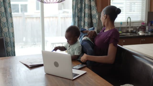two siblings play on their mothers lap as she tries to work from home - multitasking woman stock videos & royalty-free footage