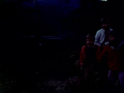 vidéos et rushes de two siblings sit on a picnic table and kick their legs. - table de pique nique