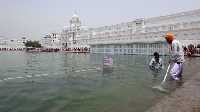 MS Two Sikh men cleaning pool at Golden Temple / Amritsar, Punjab, India