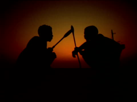 vídeos y material grabado en eventos de stock de two silhouetted basarwa men crouching down whilst holding spears at sunset, botswana - cazador