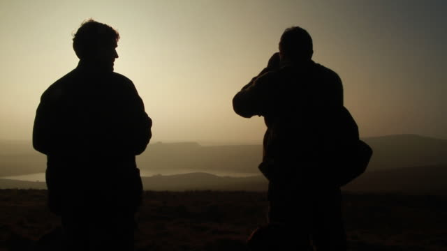 MS Two silhouetted men on top of large hill looking out at landscape with small pond and low sun / Dartmoor, England, United Kingdom
