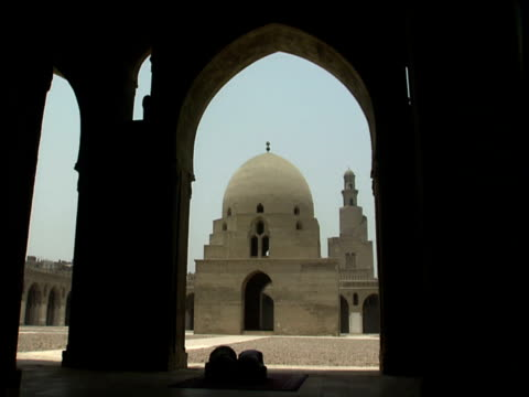 two silhouetted muslim men kneel and pray beneath arch of mosque of albtulun cairo - cairo stock videos & royalty-free footage