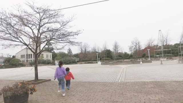 two sisters and brother playing in the park - スクエア点の映像素材/bロール