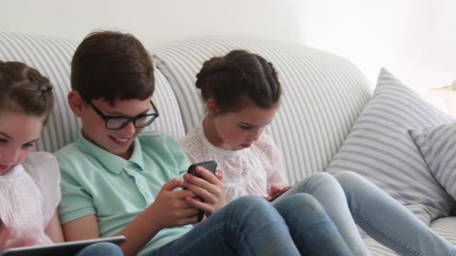 vídeos y material grabado en eventos de stock de dos hermanas y hermano utilizando dispositivos digitales en el sofá en casa - 10 11 años