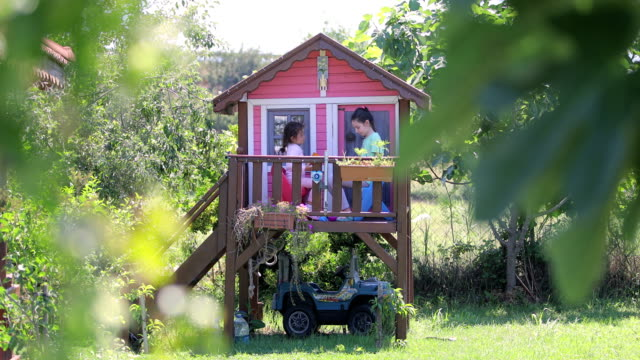 two sisters are playing in the pink tree house, kids in tree house - arranging stock videos & royalty-free footage