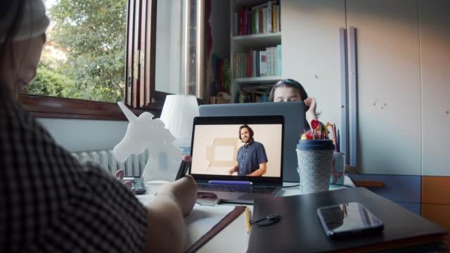 due sorelle stanno studiando insieme a casa, condividendo una scrivania per partecipare alle lezioni scolastiche online con laptop - lettore video stock e b–roll