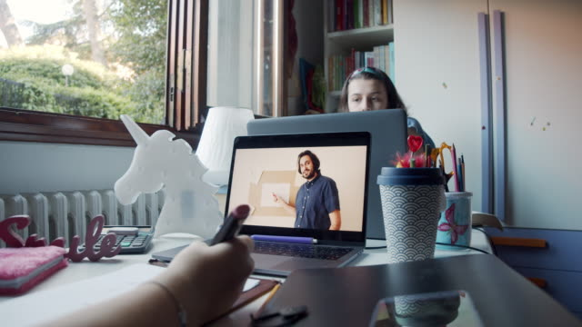 vídeos de stock e filmes b-roll de two sisters are studying together at home, sharing a desk to participate at online school lessons with laptops - 14 15 anos