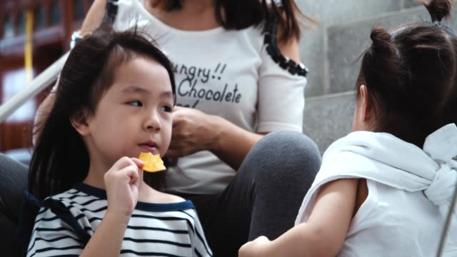 vídeos y material grabado en eventos de stock de dos hermanas disfrutando comiendo y compartiendo papas fritas - patatas fritas de churrería