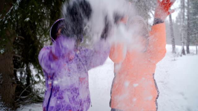 vidéos et rushes de deux soeurs ont l'amusement avec la neige sur des vacances d'hiver - neige fraîche