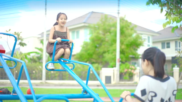 two sisters having fun together on the playground in the park. - group of objects stock videos & royalty-free footage