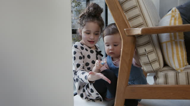 two sisters hiding behind chair and finding toy - toddler stock videos & royalty-free footage