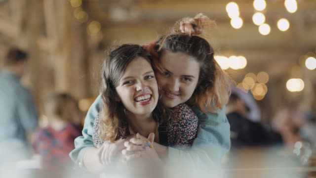 MS SLO MO. Two sisters hug and smile at camera in restaurant dining room.
