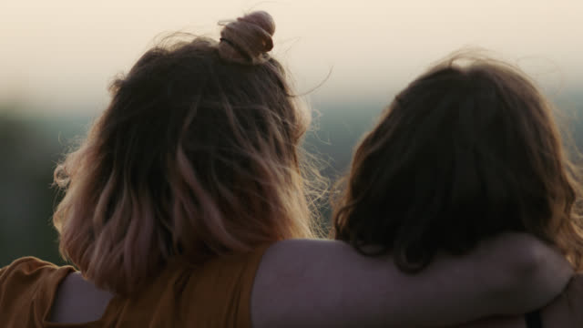 cu slo mo. two sisters hug in a field at sunset. - arm around stock videos & royalty-free footage
