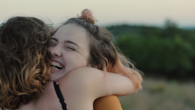 MS SLO MO. Two sisters hug in green field on mountainside.