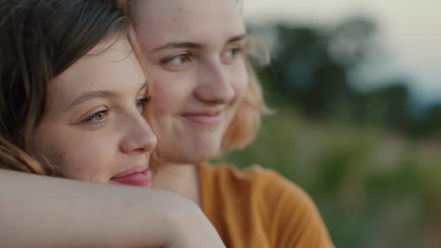 vidéos et rushes de cu slo mo. two sisters hug on green mountainside. - personnes féminines