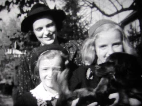 1937 two sisters in Brownie uniforms walk the dog