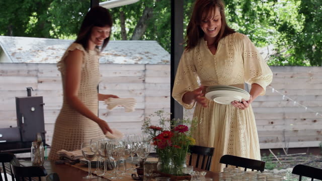 vidéos et rushes de ms pan two sisters in discussion smiling setting table for dinner on front porch of home - prendre son repas
