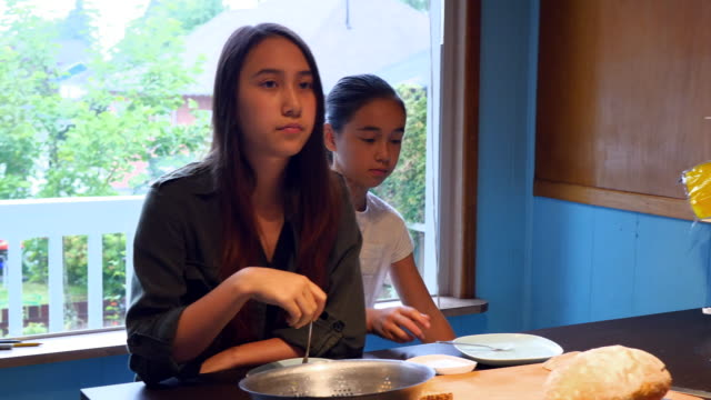 MS TU Two sisters in discussion with father while preparing breakfast together at kitchen counter before school