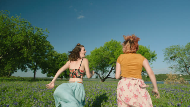 WS SLO MO. Two sisters in flowing dresses run together through field of flowers.