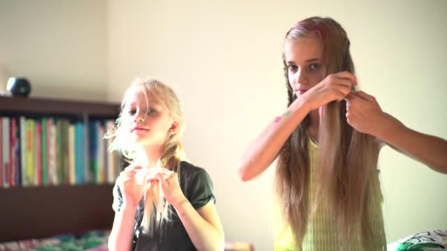 Deux sœurs dans la chambre d'enfant, sœur aînée faire cheveux robe.