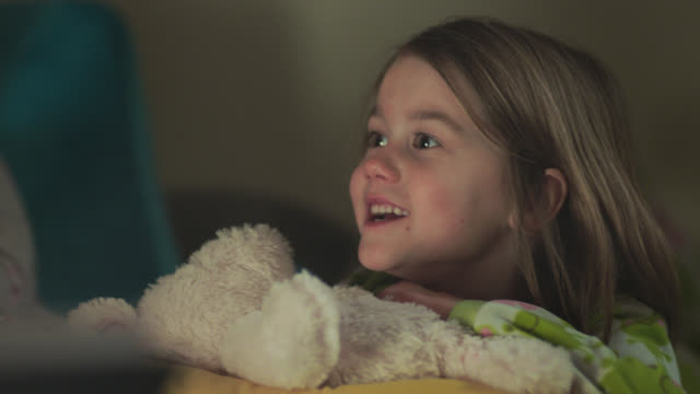 cu. two sisters in pajamas squirm in bed as dad reads bedtime story. - storytelling stock videos and b-roll footage