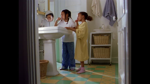 Two sisters in their pajamas brush their teeth in the bathroom.