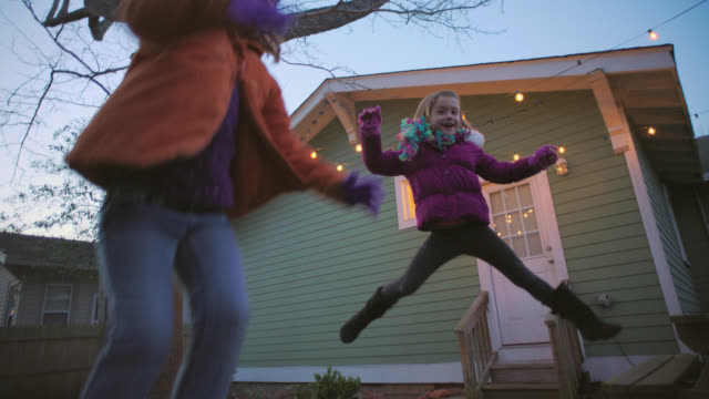 ws slo mo. two sisters jump and bounce around on trampoline in slow motion. - dusk stock videos & royalty-free footage