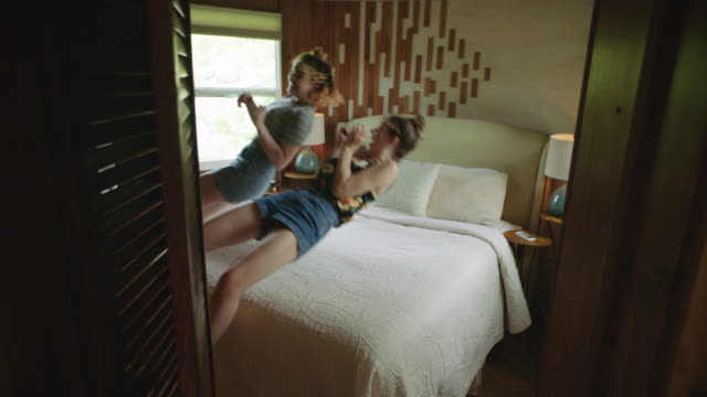 WS SLO MO. Two sisters jump onto cabin bed.
