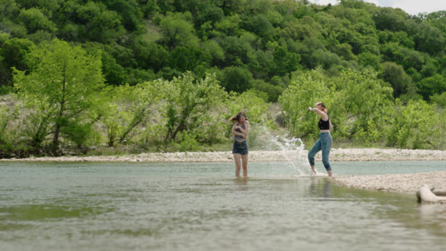 vídeos de stock, filmes e b-roll de two sisters kick up water and splash each other wading in river. - vadear