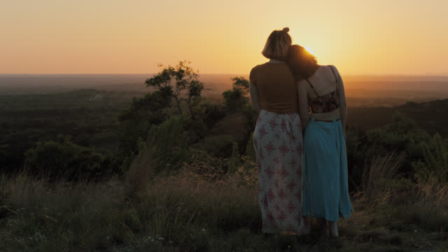 WS SLO MO. Two sisters lean on each other and watch sunset over valley from green mountainside.
