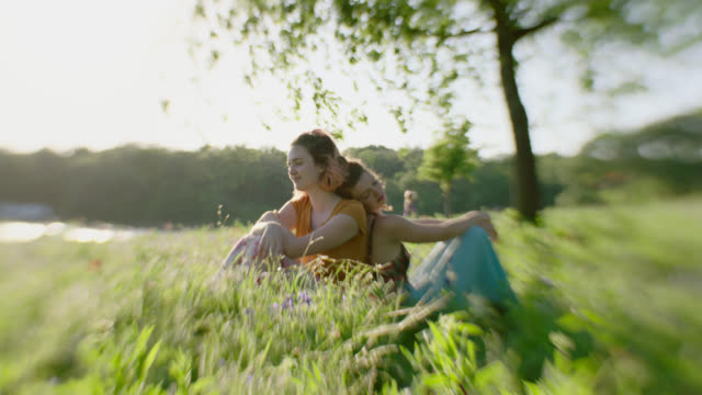 vídeos de stock, filmes e b-roll de ws slo mo. two sisters lean on each other sitting back to back in green field on summer day. - 20 24 anos