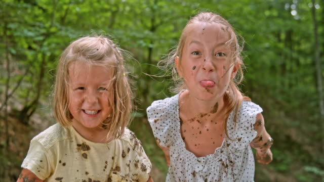 vídeos de stock e filmes b-roll de slo mo two sisters making faces into the camera while covered in mud in the forest - língua de fora