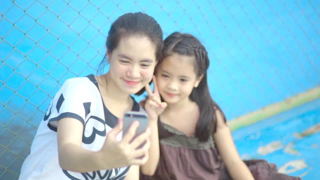 Two sisters making selfie photo on a smartphone making selfie photo on a smartphone while sitting on playgrounds.
