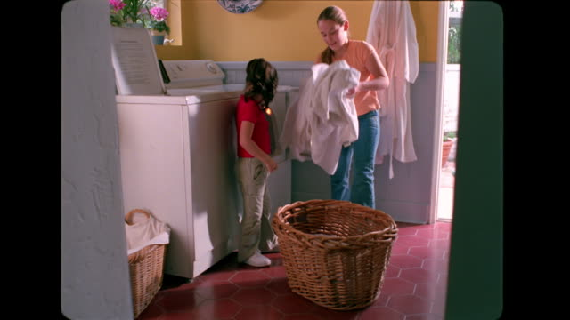 two sisters pick up laundry from the floor and put it into a basket. - laundry basket stock videos and b-roll footage