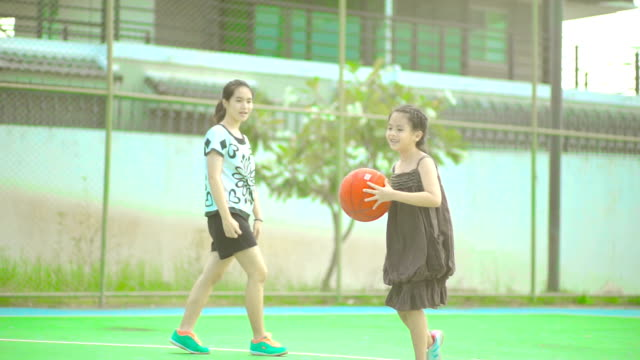 Two sisters playing basketball together at playgrounds.