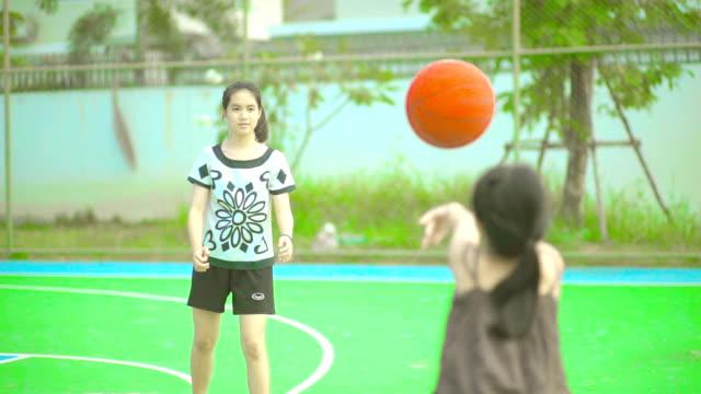 zwei schwestern zusammen spielen basketball auf spielplätzen. - basketball spielball stock-videos und b-roll-filmmaterial