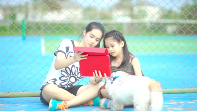 Two sisters playing games together on digital tablet computer touch screen while sitting on playgrounds.