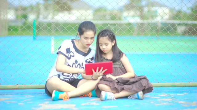 Two sisters playing games together with digital tablet computer touch screen while sitting on tennis court.