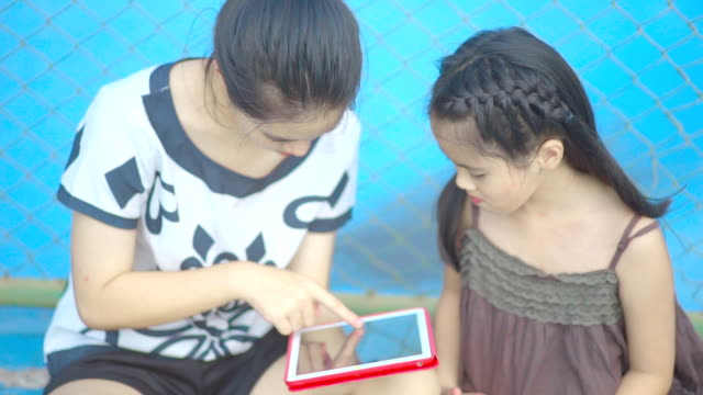 Two sisters playing games together with digital tablet computer touch screen while sitting on blue tennis court.
