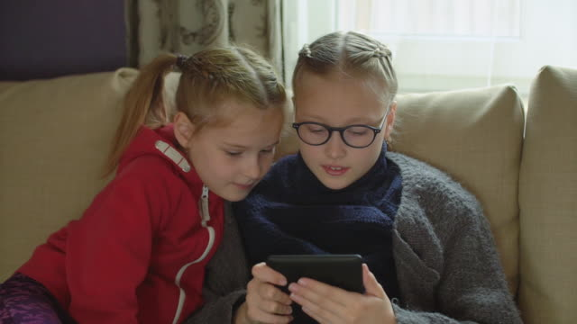 two sisters reading e-book at home on the sofa - reading glasses stock videos & royalty-free footage