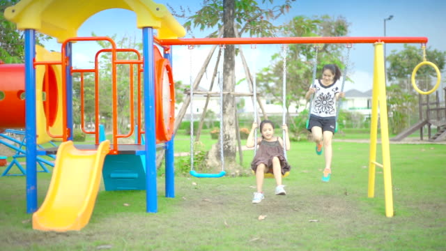 vídeos y material grabado en eventos de stock de dos hermanas en un columpio en un parque infantil en el parque. - columpiarse