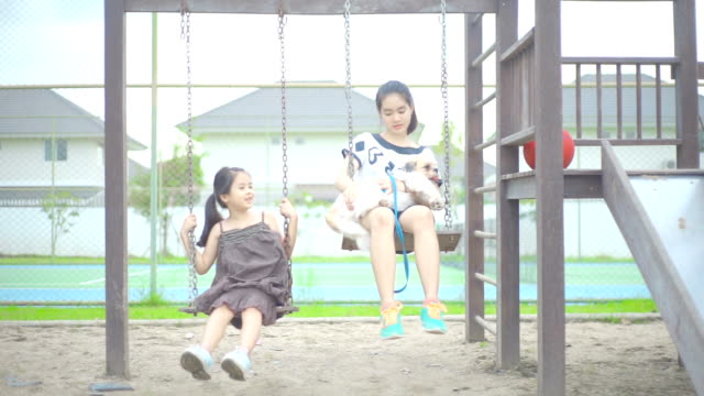 Two sisters riding on a swing at a playground in the park.