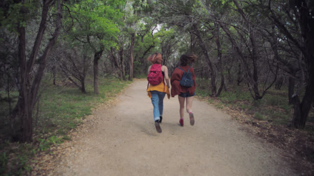 vídeos y material grabado en eventos de stock de ws slo mo. two sisters run and leap down green forest trail. - rucksack