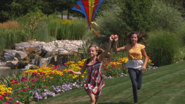SLO MO MS Two sisters (12-13, 16-17) running with kites in park / Utah, USA
